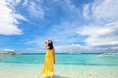 La ragazza cammina in acqua bassa sulla spiaggia tropicale fotografia stock libera da diritti