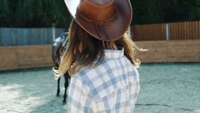 La ragazza cammina alla macchina fotografica sull'area del cavallo 4K stock footage