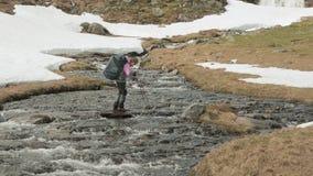 La ragazza cammina attraverso il fiume della montagna norway archivi video