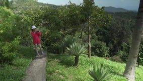 La ragazza cammina attraverso il parco tropicale e prende le immagini della bellezza del video del metraggio delle azione della n video d archivio
