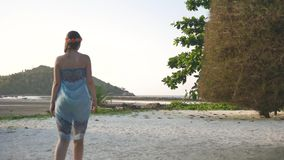 La ragazza cammina fra gli alberi tropicali archivi video
