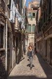 La ragazza cammina giù un vicolo soleggiato a Venezia Immagine Stock