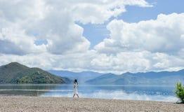 La ragazza cammina lungo la banca del lago Lugu immagini stock