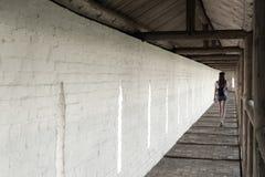 La ragazza cammina lungo la navata laterale lunga del monastero contro lo sfondo di una parete bianca immagini stock