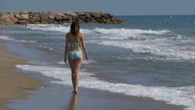 La ragazza cammina lungo la spiaggia della costa di mare al rallentatore video d archivio
