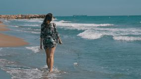 La ragazza cammina lungo la spiaggia della costa di mare al rallentatore archivi video
