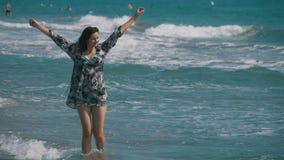 La ragazza cammina lungo la spiaggia della costa di mare al rallentatore stock footage