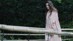 La ragazza cammina lungo un ponte di bambù autentico nel parco archivi video