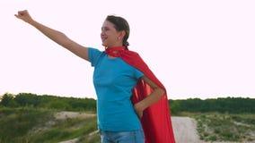 La ragazza cammina in un'espressione rossa del mantello dei sogni sogni della ragazza di trasformarsi in un supereroe Bello super video d archivio