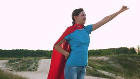 La ragazza cammina in un'espressione rossa del mantello dei sogni sogni della ragazza di trasformarsi in un supereroe Bello super stock footage