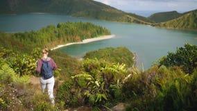 La ragazza cammina vicino ad un lago della montagna ad un'altezza che trascura l'oceano archivi video