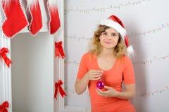La ragazza in cappello di Santa è decorata con un camino Immagine Stock