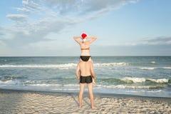La ragazza in cappello di Santa si siede sulle spalle di un tipo Puntello di mare Vista posteriore Immagini Stock Libere da Diritti