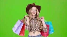 La ragazza in cappello e stivali di cowboy viene con le borse in sue mani Schermo verde archivi video