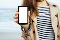 La ragazza in cappotto beige e maglietta a strisce mostra un fon dello schermo in bianco fotografia stock