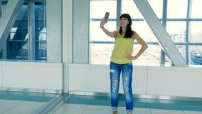 La ragazza castana abbastanza giovane fa il selfie, nell'incrocio del sottopassaggio, facendo uso dello Smart Phone, stock footage