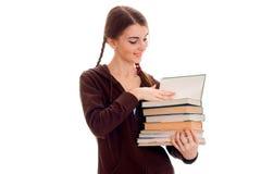 La ragazza castana allegra alla moda dello studente con le trecce negli sport marroni copre con i libri della sua posa delle mani Fotografia Stock Libera da Diritti