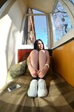 La ragazza castana attraente si siede accanto ad uno smartph moderno di tocco fotografia stock libera da diritti