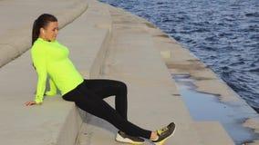 La ragazza castana caucasica in panno di sport si rilassa sull'argine che ascolta la musica stock footage