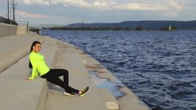 La ragazza castana caucasica in panno di sport si rilassa sull'argine che ascolta la musica archivi video