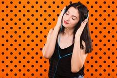 La ragazza castana con le cuffie su fondo arancio con il nero fa Fotografia Stock Libera da Diritti