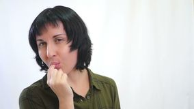 La ragazza castana con piacere mangia le patatine fritte su un fondo bianco stock footage