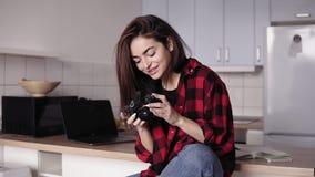 La ragazza castana di Attarctive sta provando a cambiare le regolazioni della macchina fotografica mentre si sedeva nella sua cuc video d archivio