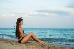 La ragazza castana si siede sulla spiaggia Fotografie Stock