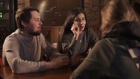 La ragazza castana in una società dei suoi amici sta parlando alla tavola in caffè archivi video