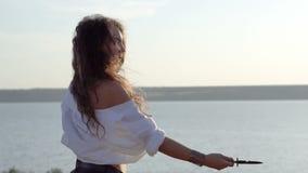 La ragazza castana zingaresca riccia manipola con il coltello del pugnale sul pendio del golfo video d archivio