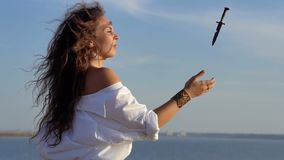 La ragazza castana zingaresca riccia manipola con il coltello del pugnale sul pendio del golfo Movimento lento video d archivio