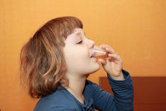 La ragazza cattura la medicina. Beve lo sciroppo Fotografia Stock