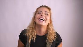 La ragazza caucasica piacevole è ridere rilassata alla macchina fotografica e mostrare la felicità su fondo grigio video d archivio
