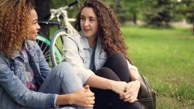 La ragazza caucasica sta parlando con suo amico afroamericano grazioso che si siede nel parco sull'erba con le biciclette nel fon stock footage