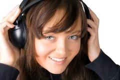 La ragazza che ascolta la musica tramite i trasduttori auricolari Fotografia Stock