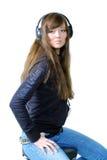 La ragazza che ascolta la musica tramite i trasduttori auricolari Fotografia Stock Libera da Diritti