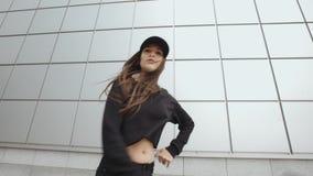 La ragazza che balla, esegue lo stile libero contemporaneo nella via, ambiente urbano di ballo hip-hop moderno archivi video