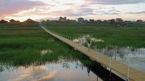 La ragazza che cammina sul ponte di legno, lago al tramonto, antenna del fuco segue il colpo stock footage