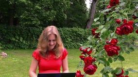 La ragazza che chiacchiera il computer portatile online si siede alle rose di fioritura del cespuglio in parco video d archivio