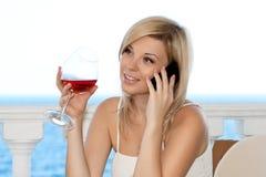 La ragazza che comunicano sul telefono in un caffè e la bevanda wine immagine stock