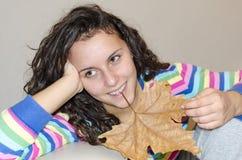 la ragazza che considera il lato con ad una foglia di autunno ha tenuto nella sua bocca fotografia stock
