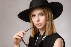 La ragazza che distoglie lo sguardo in cappello tiene gli occhiali da sole vicino al fronte Immagine Stock Libera da Diritti