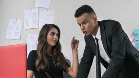 La ragazza che flirta con un impiegato in un vestito nell'ufficio, tocca delicatamente la sua guancia, lui di fronte a, flirt, mo video d archivio
