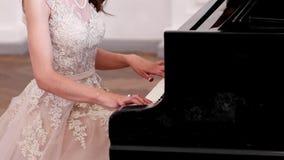 La ragazza che gioca il piano, concerto, bella, figura esile di una giovane donna si è vestita in vestito elegante, dita tocca video d archivio