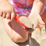 La ragazza che gioca nella sabbiera getta il mestolo di rosso della sabbia Fotografia Stock