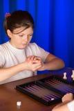 La ragazza che gioca un gioco da tavolo ha chiamato Backgammon immagini stock libere da diritti