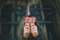 La ragazza che giudica un cuore a forma di ha decorato il pan di zenzero, Fotografia Stock Libera da Diritti