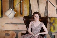 La ragazza che il castana in un bello vestito posa la seduta in un sedile contro lo sfondo della parete ha pubblicato nello stile fotografia stock