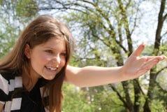 La ragazza che indica con lei distribuisce Fotografia Stock Libera da Diritti