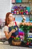 La ragazza che lavora in un negozio di fiore, donna del fiorista fa un mazzo Immagini Stock